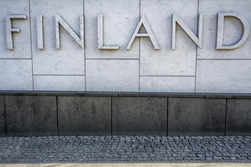Finland raised sign on marble wall in Helsinki. Bold lettering in the Finnish capital on wall above cobbled street stock photos