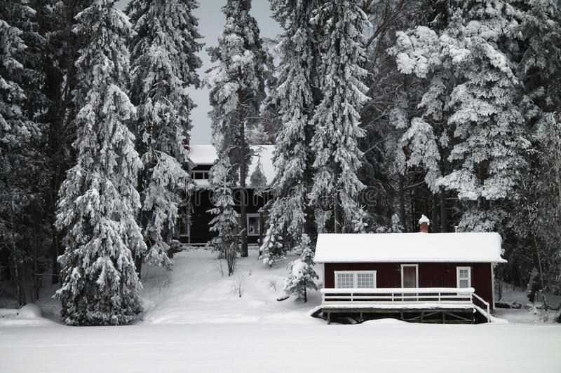 Finland: Wintery forest. Sauna and a house by a frozen lake in Southern Finland royalty free stock image