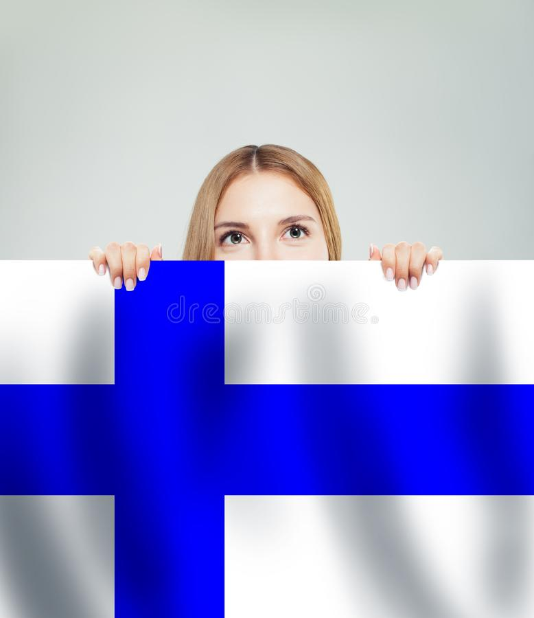 Finland. Young happy woman with the Finnish flag background royalty free stock photo
