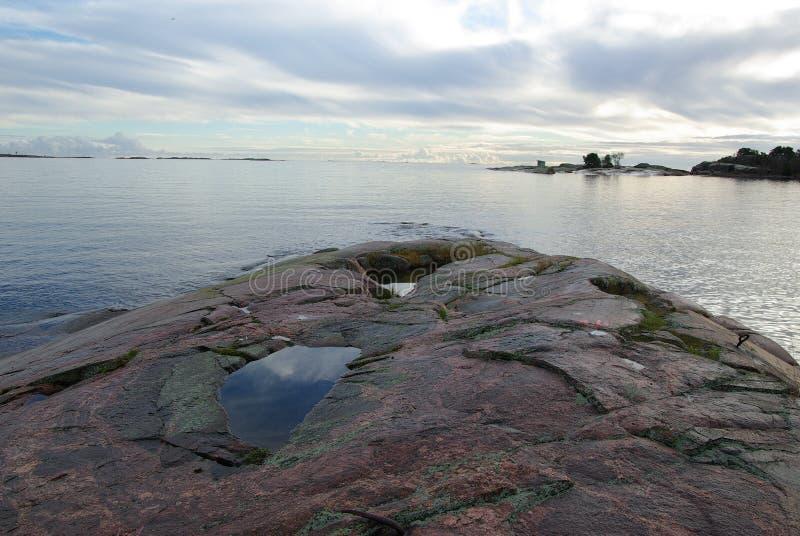 Finlandia, Hanko, zmierzch, niebo odbijał w kamieniu zdjęcie stock