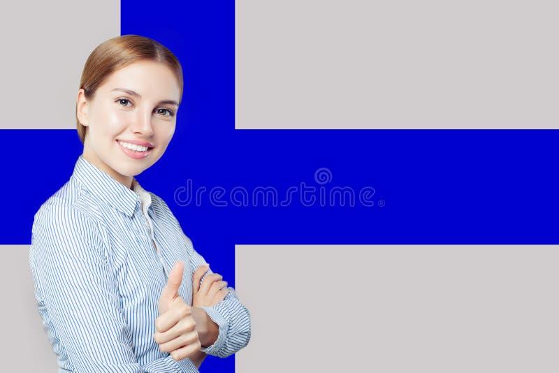 Finlandia Młoda szczęśliwa śliczna dziewczyna z kciukiem przeciw w górę Fińskiego chorągwianego tła Studencki lub biznesowy pojęc obraz stock
