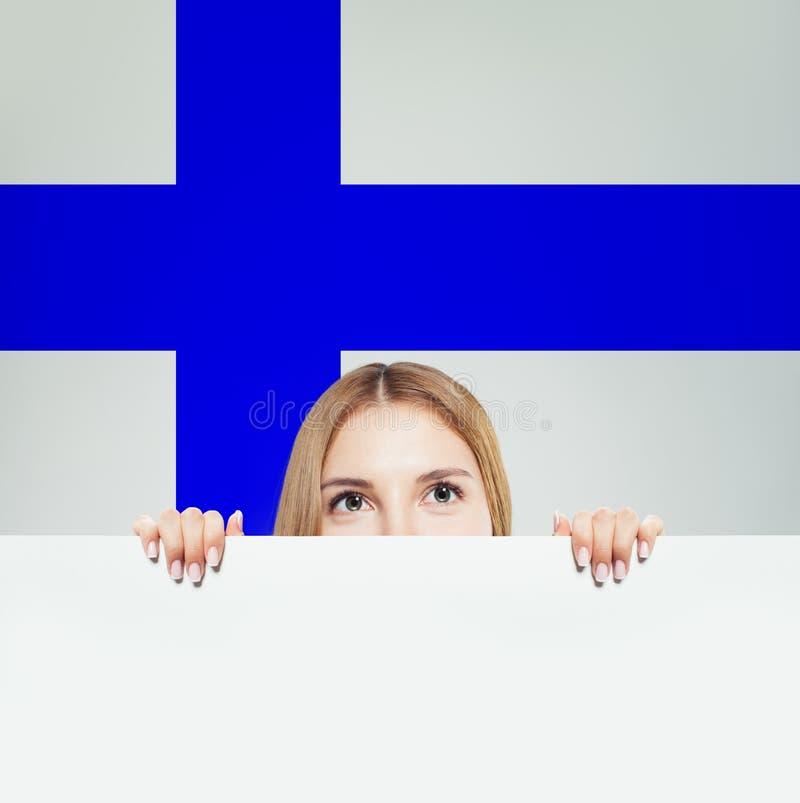 Finlandia Młoda szczęśliwa kobieta z białą księgą przeciw Fińskiemu chorągwianemu tłu fotografia royalty free