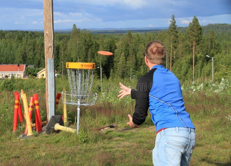 Finlandia, Savonia: Jogador de golfe do disco que joga na cesta do alvo imagens de stock