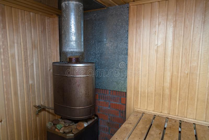 Finlandssvensk bastu med ett ångarum som dekoreras med trä med en ugn och stenar på den för tvätt arkivbild