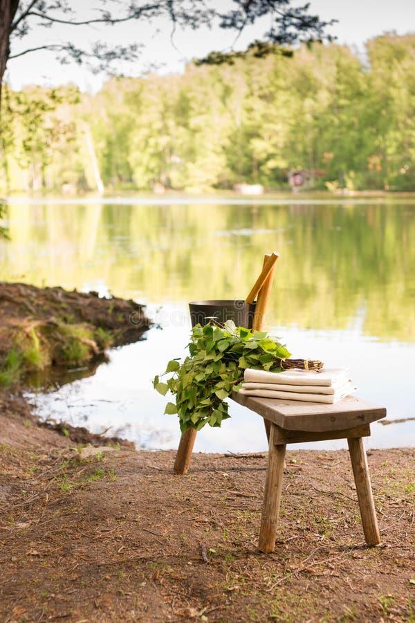 Finlandssvenska sommarlandskap- och bastuobjekt på bänk vid sjön royaltyfri fotografi