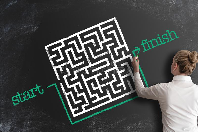 Finna idérikt lösningsbegrepp med kvinnan som kopplar förbi labyrinten, genom att dra linjen runt om den arkivfoton