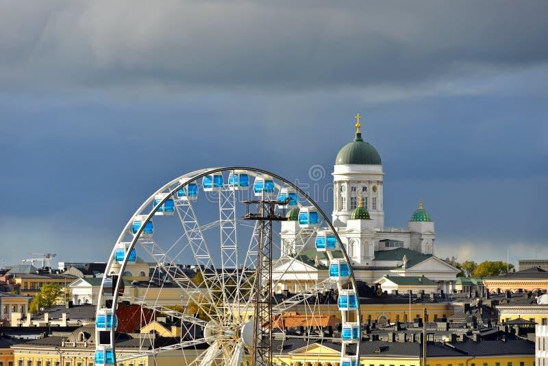 Finnair SkyWheel και φινλανδικός εβαγγελικός λουθηρανικός καθεδρικός ναός της επισκοπής του Ελσίνκι 1852 στο υπόβαθρο του σκοτειν στοκ φωτογραφίες