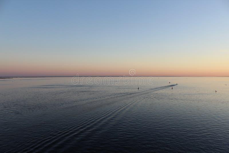 Finnisches Meerbusen am Abend, die blaue Seespur vom Boot und rosa Licht im Himmel lizenzfreies stockbild