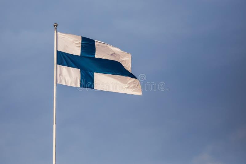Finnish flag against the blue sunny sky stock photography