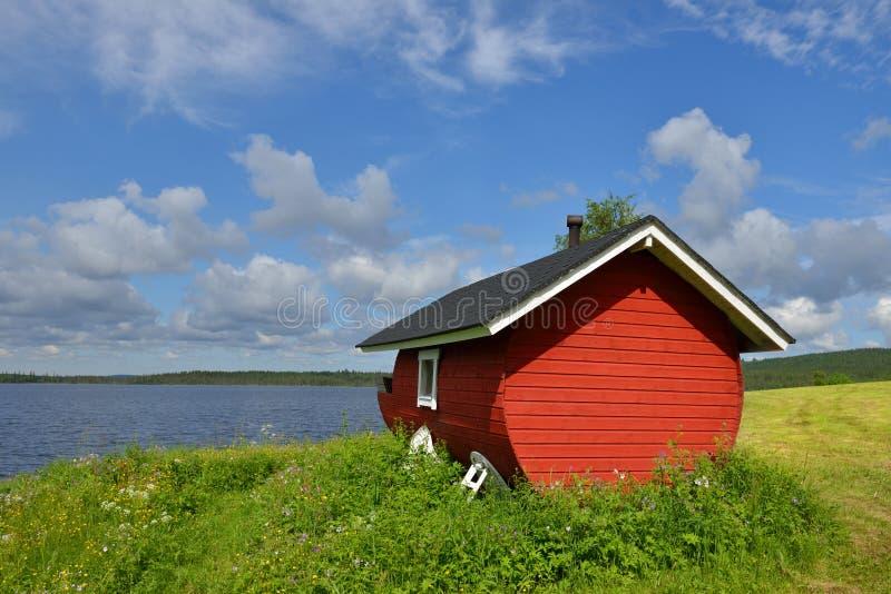 Finnish sauna on shore of blue lake stock photography