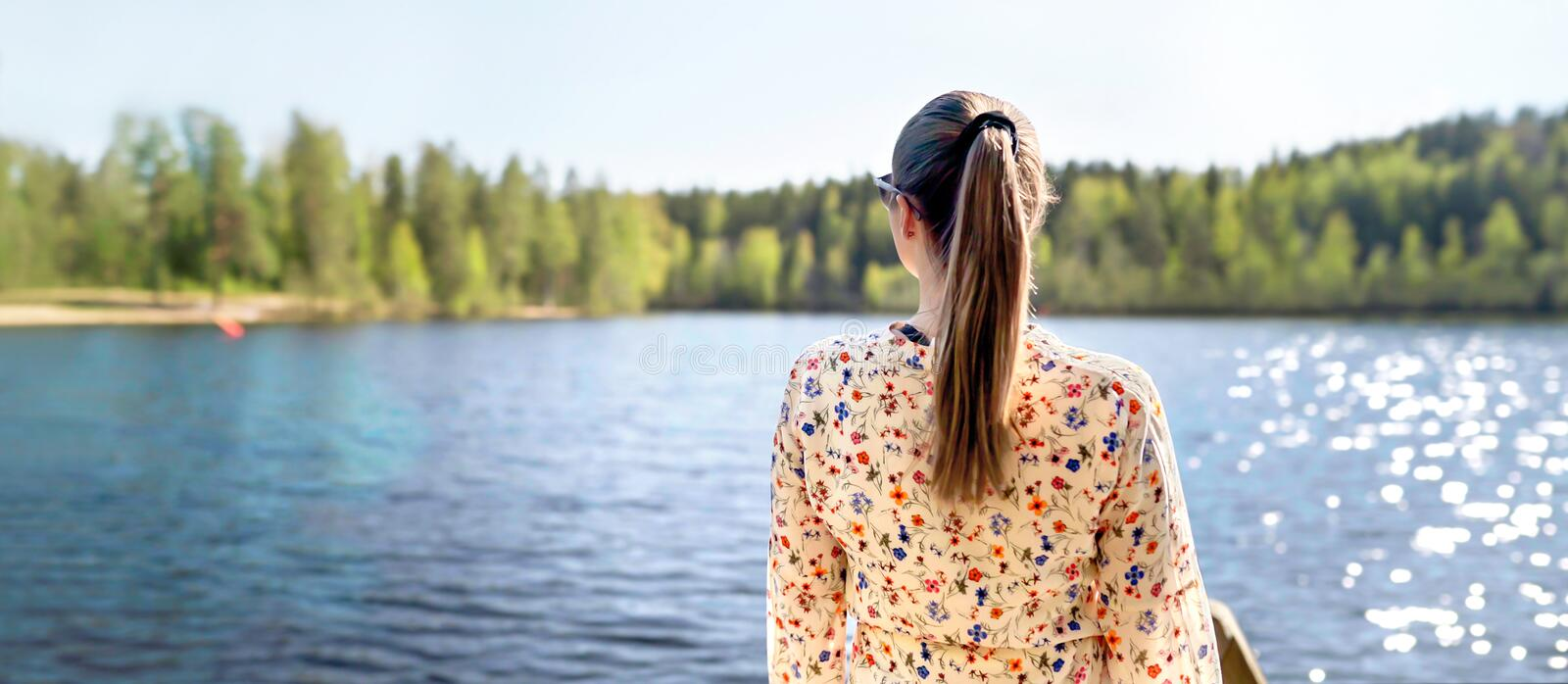 Finnish woman standing and looking at a lake in Finland. Happy person relaxing and enjoying sunny summer vacation or weekend. royalty free stock photos