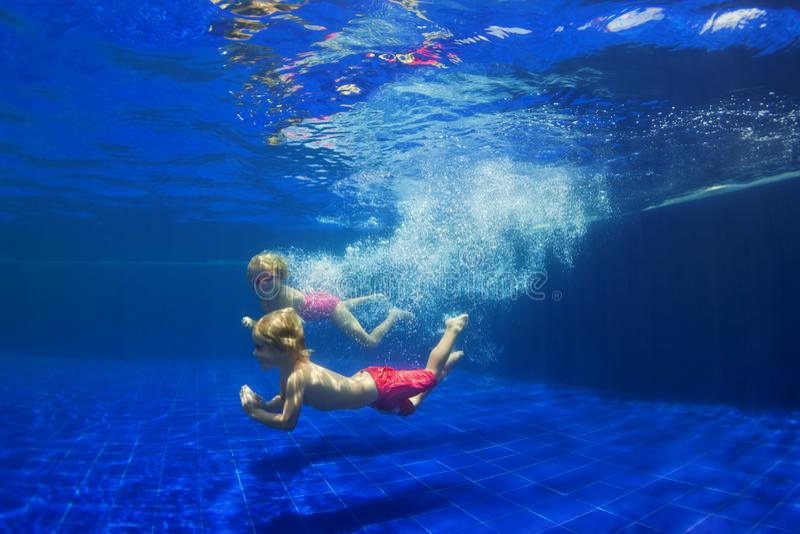Finny kids dive underwater in swimming pool stock photos