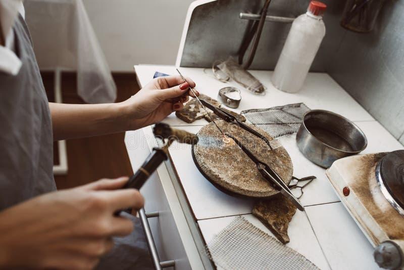 fint arbete Sidosikt av juvelerares händer som löder ett silverörhänge med flamman från svetsningsfacklan royaltyfri bild