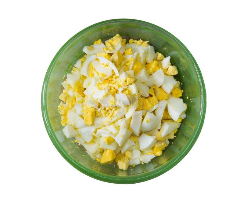 Fint - högg av kokta ägg i en grön bunke som isoleras på vit bakgrund arkivfoto
