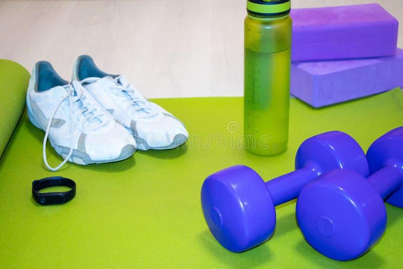 Fintes hantlar, gymnastikskor, en flaska av vatten, konditionarmband och purpurf?rgade kuber p? ett gr?nt mattt, sportbegrepp royaltyfri bild