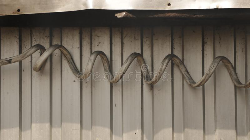 Fio bonde espiral sujo gigante na parede do ferro ondulado foto de stock royalty free