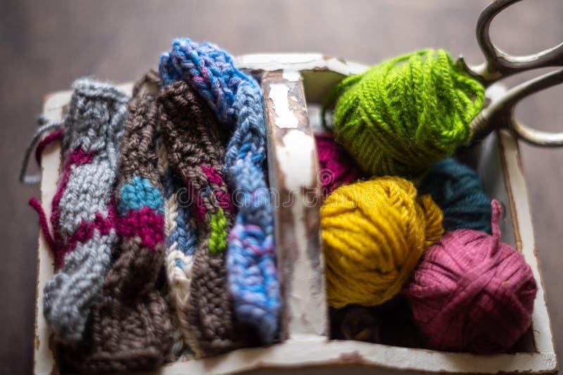 Fio a cores para tricô, tricô, tesoura vintage em caixa branca foto de stock