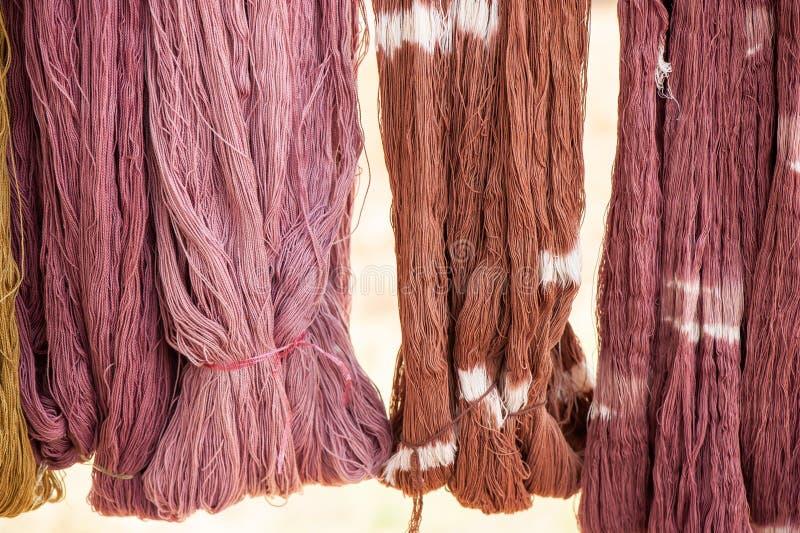 Fio de algodão que tinge-se com as tinturas naturais que penduram na luz solar para secar Produtos feitos a mão locais da provínc foto de stock