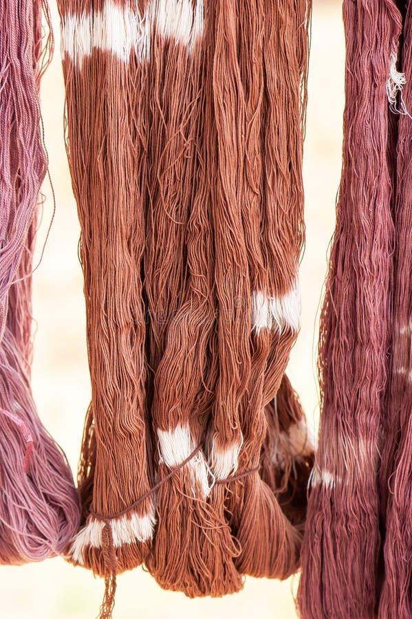 Fio de algodão que tinge-se com as tinturas naturais que penduram na luz solar para secar Produtos feitos a mão locais da provínc foto de stock royalty free