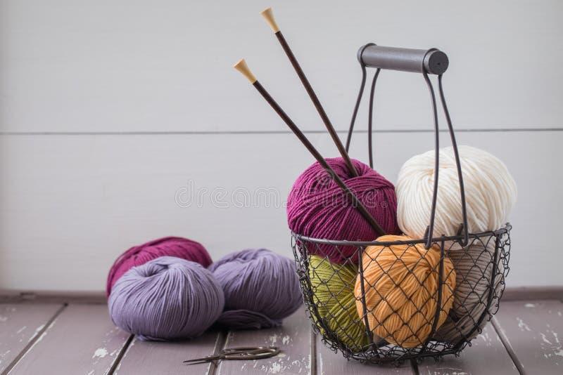 Fio de lãs colorido da mola em uma cesta do ferro com as agulhas de confecção de malhas de madeira fotos de stock