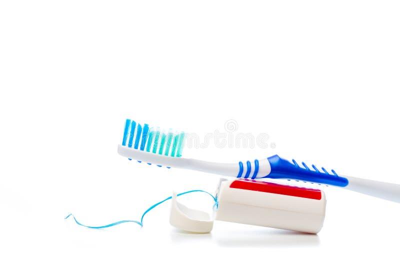 Fio dental e escova de dentes em um fundo isolado fotografia de stock royalty free