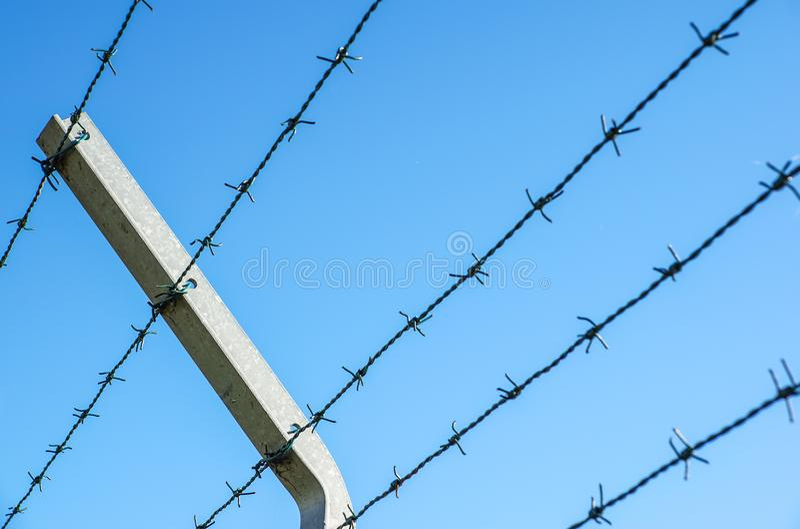 Fio enrolado da lâmina com suas farpas de aço afiadas sobre uma cerca de perímetro da malha assegurando a segurança fotografia de stock royalty free