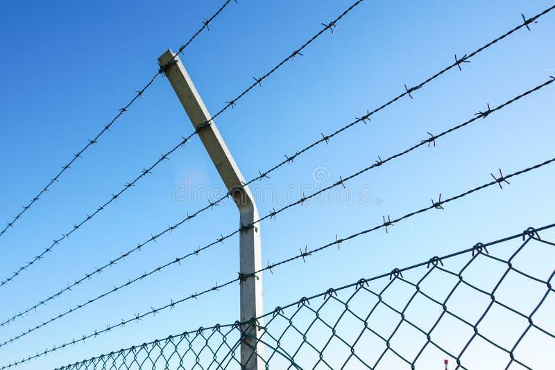 Fio enrolado da lâmina com suas farpas de aço afiadas sobre uma cerca de perímetro da malha assegurando a segurança imagens de stock royalty free