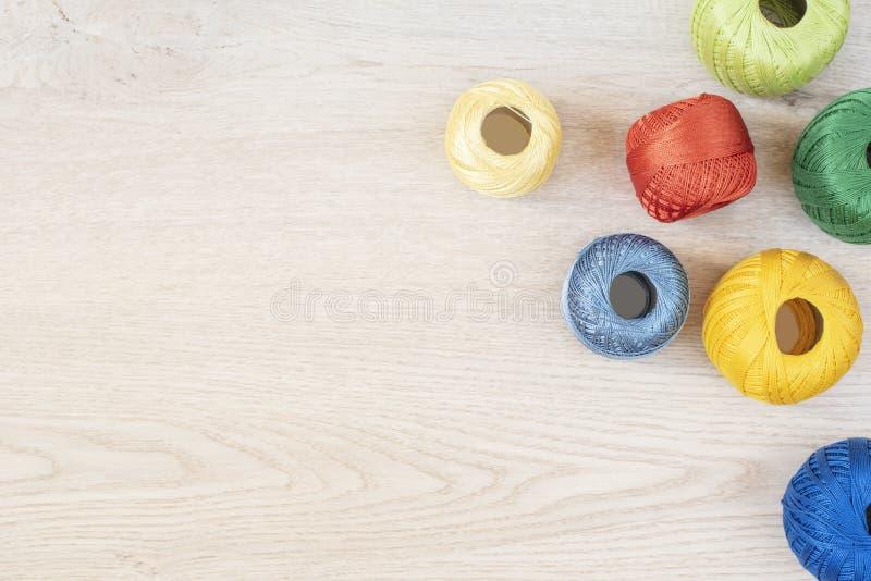 Fio para confecção de malhas no fundo de madeira Ajuste das linhas coloridas para fazer crochê no fundo de madeira cinzento, vist fotos de stock royalty free