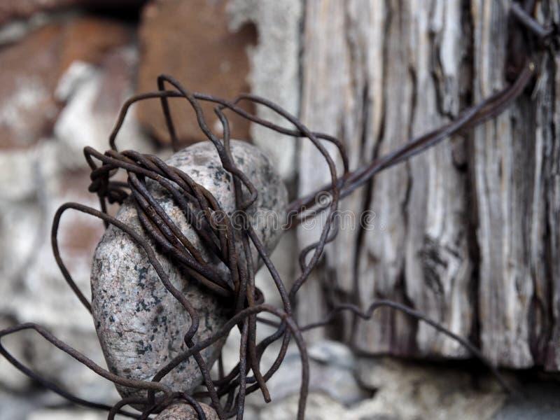 Fio velho unido à parede de pedra e de madeira que envolve a rocha fotografia de stock