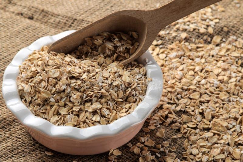 Fiocchi asciutti della farina d'avena in una ciotola ed in un cucchiaio di legno su una tavola di legno marrone Nutrizione sana A fotografia stock libera da diritti