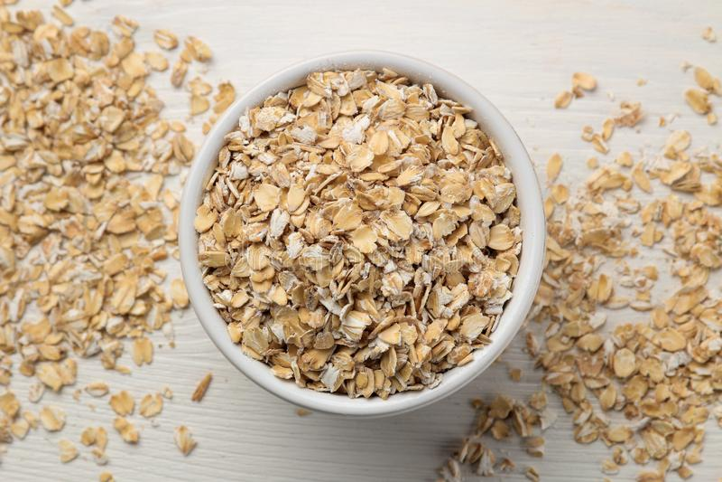 Fiocchi asciutti della farina d'avena in una ciotola su una tavola di legno bianca Nutrizione sana Alimento sano Vista superiore immagine stock libera da diritti