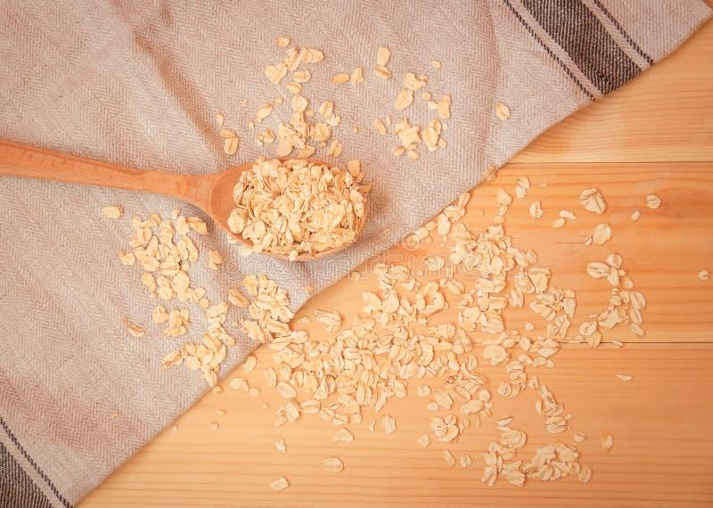 Fiocchi di avena o fiocchi di avena in cucchiaio di legno Stile di vita sano, concetto sano di cibo immagini stock libere da diritti