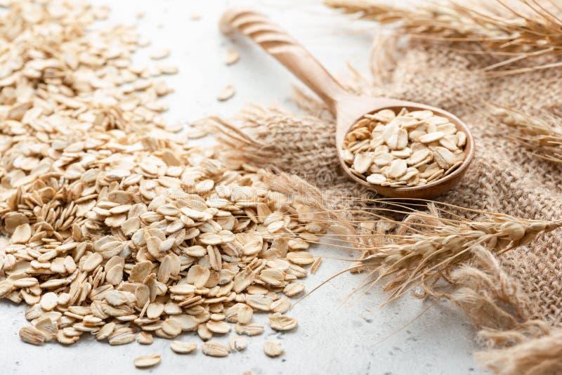 Fiocchi di avena, orecchie di grano e cucchiaio di legno fotografie stock