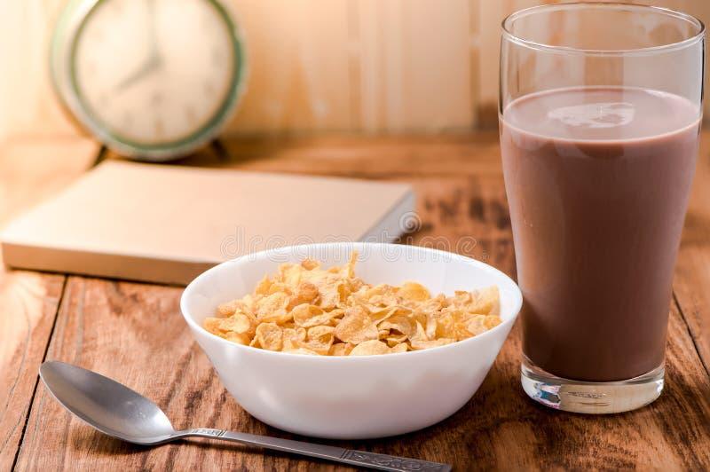 Fiocchi di granturco cereale e latte al cioccolato sulla tavola di legno fotografia stock libera da diritti