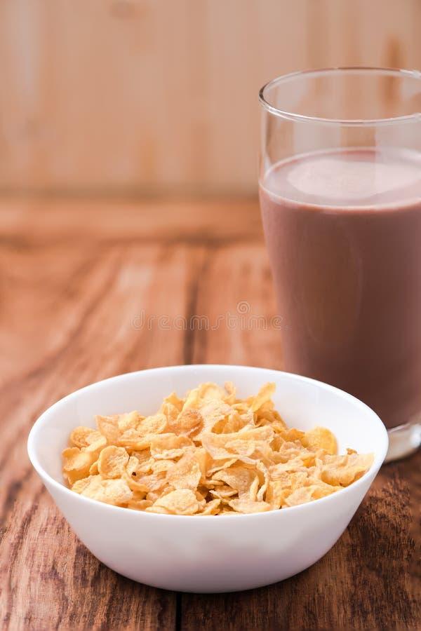 Fiocchi di granturco cereale e latte al cioccolato sulla tavola di legno fotografia stock