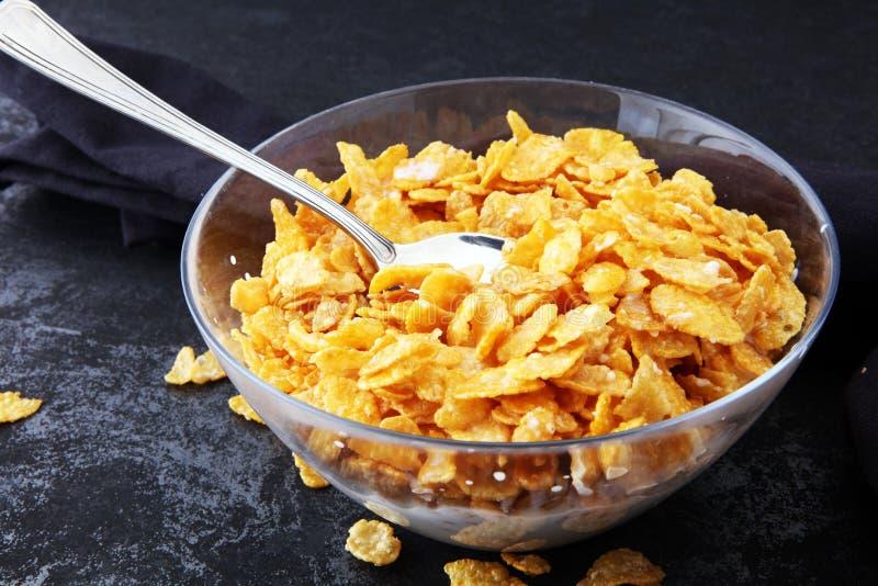 Fiocchi di granturco cereale e latte in una ciotola di vetro Prima colazione co di mattina fotografia stock