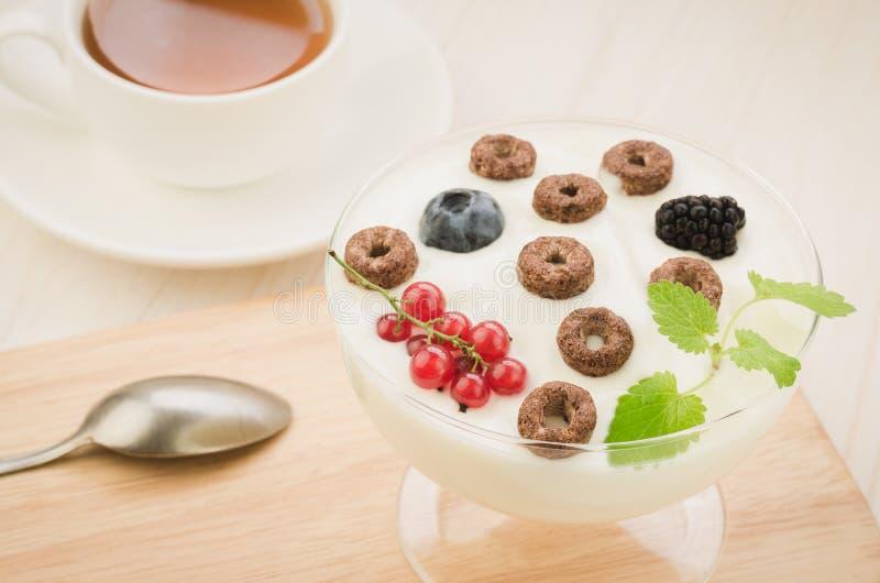 Fiocchi di granturco con le bacche, il yogurt ed il tè per la prima colazione/fiocchi di granturco del cioccolato con le bacche,  immagine stock libera da diritti