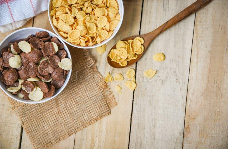 Fiocchi di granturco della prima colazione e diversi cereali in tazza del latte e della ciotola su fondo di legno per l'alimento  fotografie stock libere da diritti