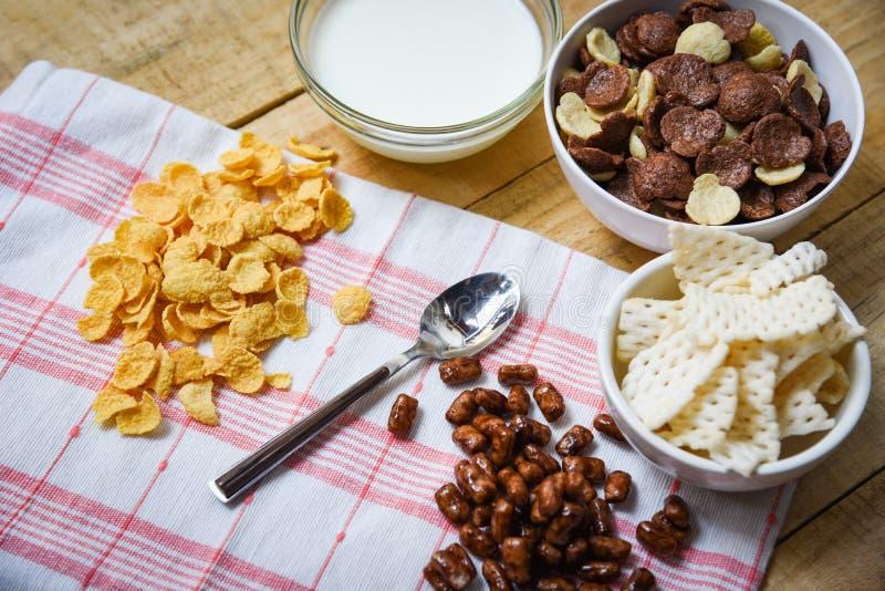 Fiocchi di granturco della prima colazione e diversi cereali in tazza del latte e della ciotola su fondo di legno per l'alimento  immagini stock libere da diritti
