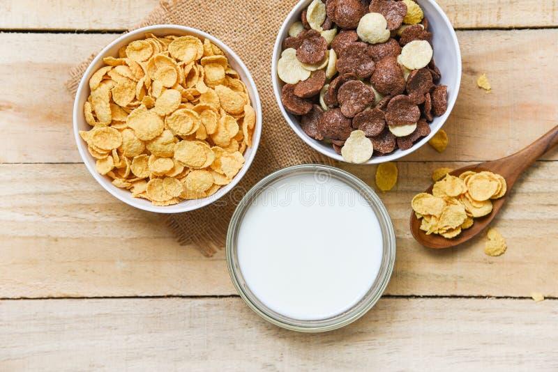 Fiocchi di granturco della prima colazione e diversi cereali in tazza del latte e della ciotola su fondo di legno per l'alimento  fotografia stock libera da diritti