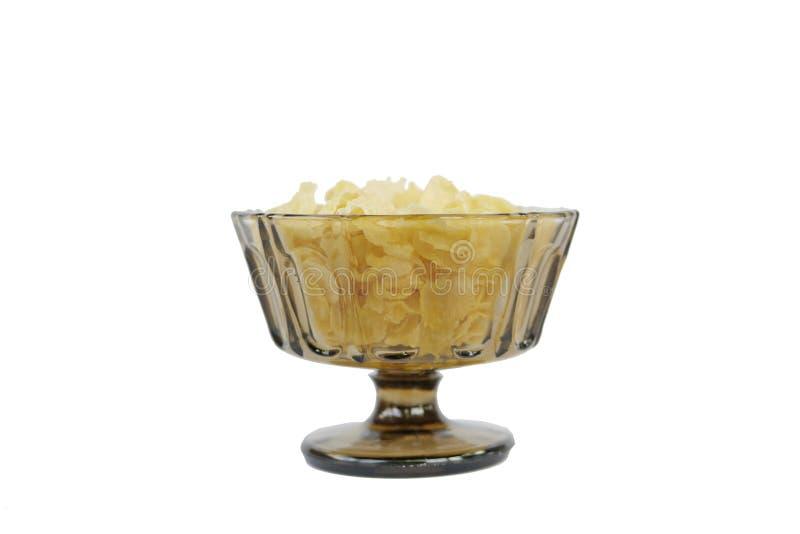 Fiocchi di granturco in una ciotola di vetro tradizionale brunastra con il supporto Sparato dalla parte anteriore immagini stock libere da diritti