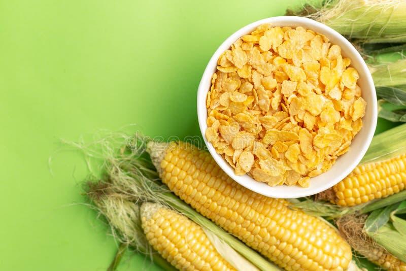 Fiocchi di mais in ciotola bianca vicino alle pannocchie di granturco immagini stock