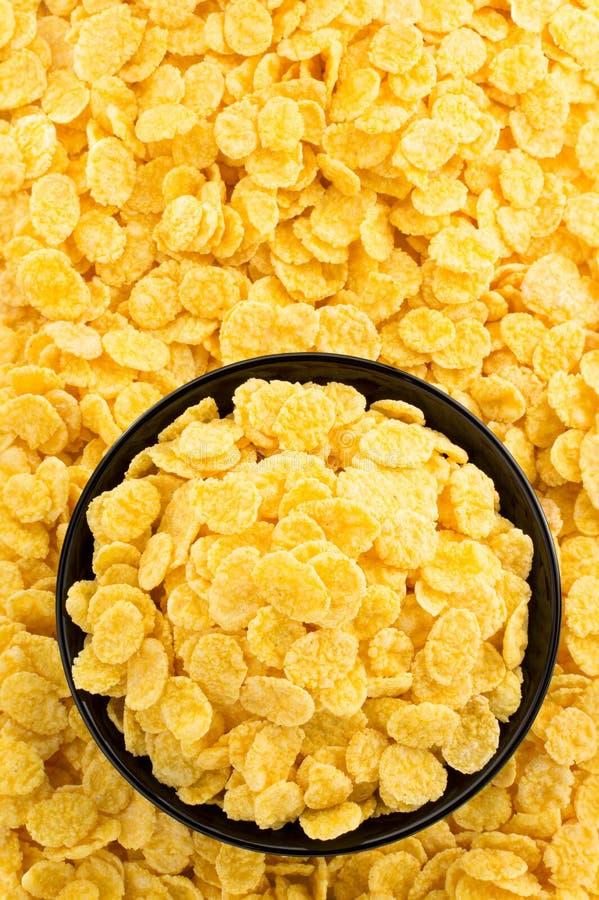 Fiocchi di mais in ciotola come fondo immagine stock