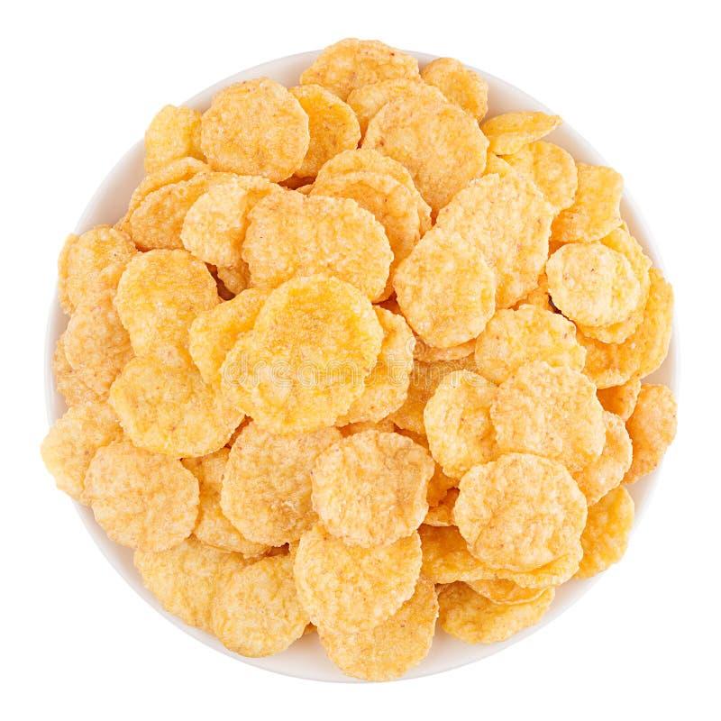 Fiocchi di mais dorati in ciotola bianca isolata, vista superiore cereali fotografia stock libera da diritti
