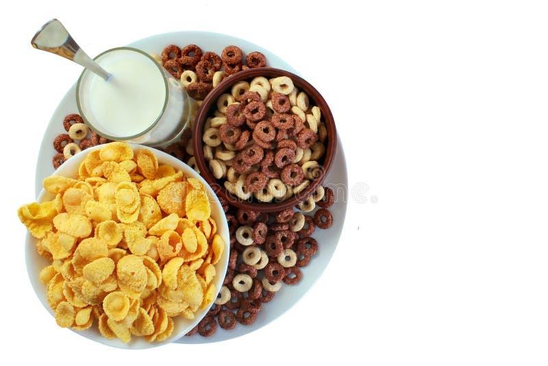 Fiocchi di mais e bicchiere di latte isolati su fondo bianco immagine stock libera da diritti