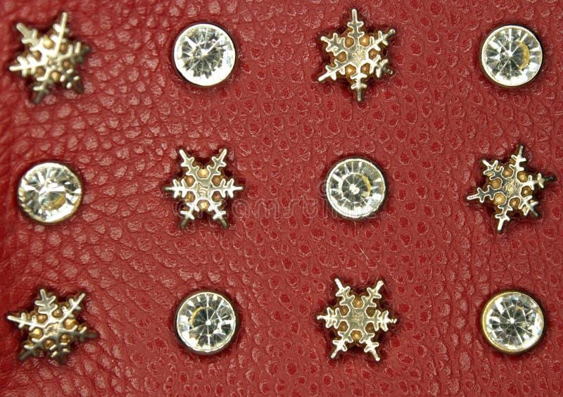 Fiocchi di neve e diamanti dell'oro su pelle rossa fotografia stock libera da diritti
