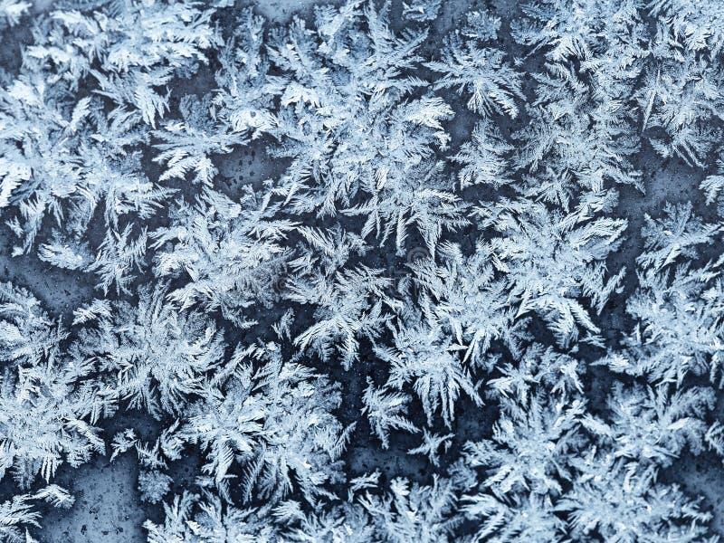 Fiocchi di neve e gelo sulla fine del vetro di finestra su immagini stock libere da diritti