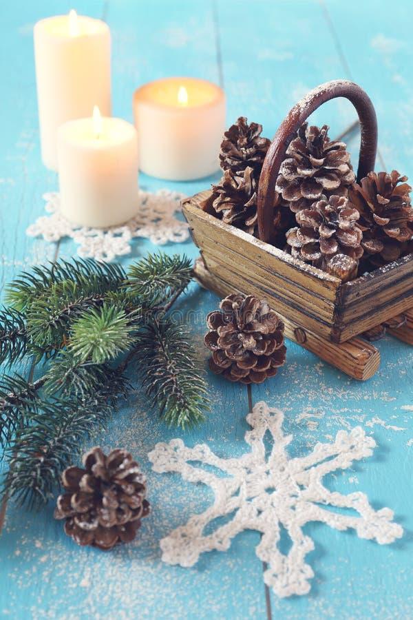 Fiocco di neve a foglie rampanti, merce nel carrello delle pigne e candela bruciante fotografia stock libera da diritti