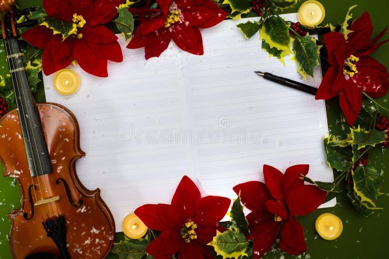 Fiol och öppet musikmanuskript på den gröna bakgrunden Julfilial och klockor royaltyfri bild