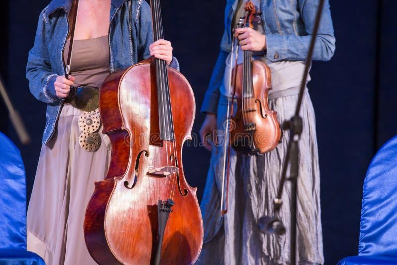 Fiol och violoncell i kvinnahänder på konsert arkivbilder